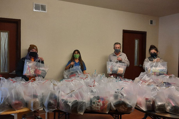 Santa Fe Quota Lions Club Branch member, club friend, and Street Outreach Staff with completed bags.